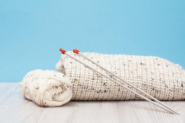 Weißer pullover und garnstränge mit metallstricknadeln auf grauen brettern und blauem hintergrund. strickkonzept.