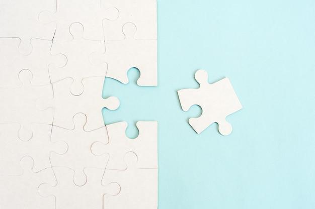 Weißer puzzle-hintergrund mit fehlendem stück auf blauem hintergrund. draufsicht
