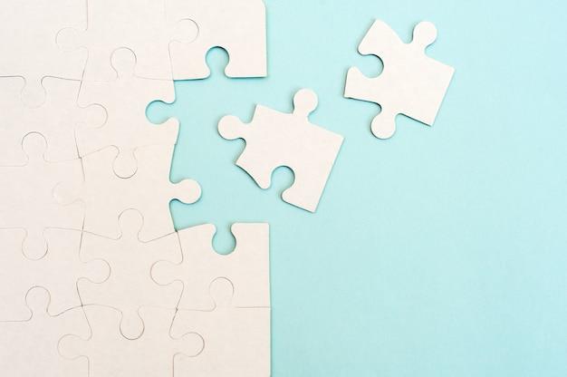 Weißer puzzle-hintergrund mit fehlendem stück auf blauem hintergrund.