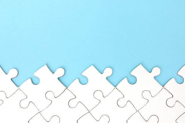 Weißer puzzlespielrahmen auf blauem pastellhintergrund mit kopienraum