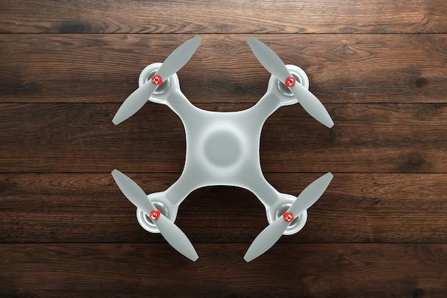 Weißer quadrocopter auf hölzernem braunem hintergrund