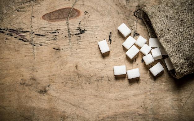 Weißer raffinierter zucker in der tasche auf holztisch.