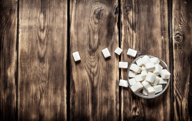 Weißer raffinierter zucker in der tasse. auf holztisch.