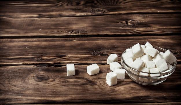 Weißer raffinierter zucker in der tasse auf holztisch.
