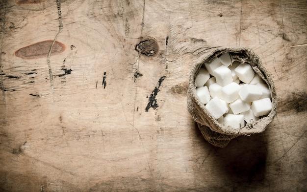 Weißer raffinierter zucker in der tüte. auf dem hölzernen hintergrund.