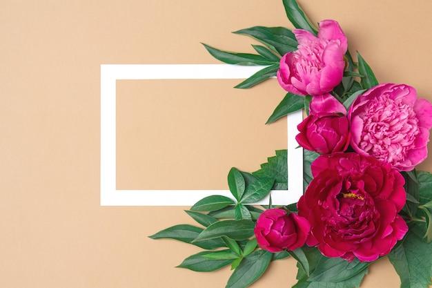 Weißer rahmen auf hellbrauner pastelloberfläche mit rosa blüten pfingstrosen