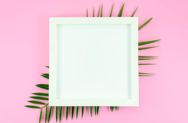 Weißer rahmen der flachen lage am rosa hintergrund mit tropischen blättern von der palme