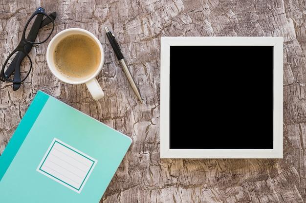 Weißer rahmen; kaffeetasse; brille; stift und notizbuch auf strukturierten hintergrund