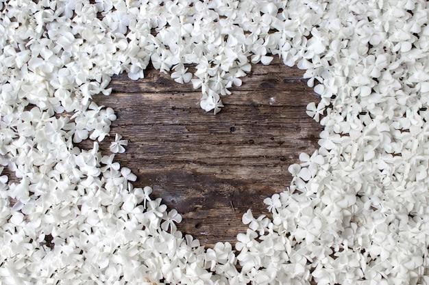 Weißer rahmen leer, blütenblätter für spa oder hochzeitsmodell auf draufsicht des hölzernen hintergrundes. schöne blumen