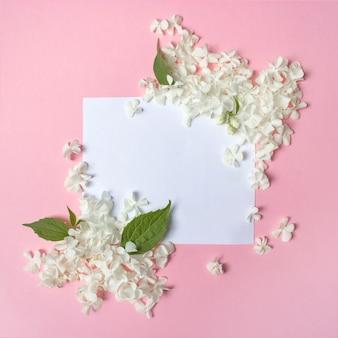 Weißer rahmen leer, blütenblätter für spa oder hochzeitsmodell auf rosa rückenansicht von oben. zarte blumengrenze