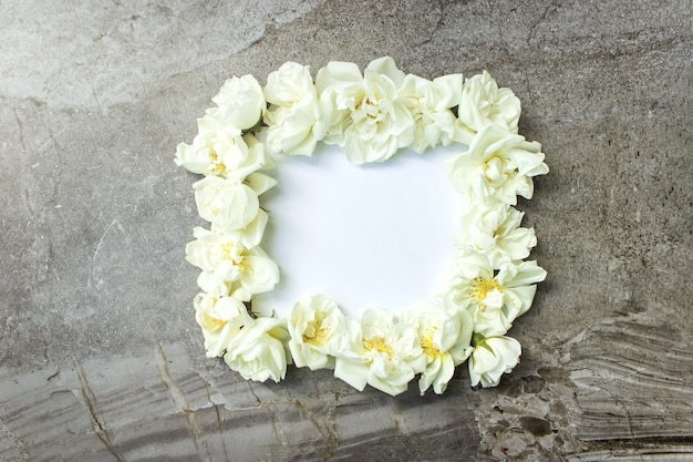 Weißer rahmen leer, blütenblätter für spa oder hochzeitsmodell grauer hintergrund draufsicht. schöne blumen
