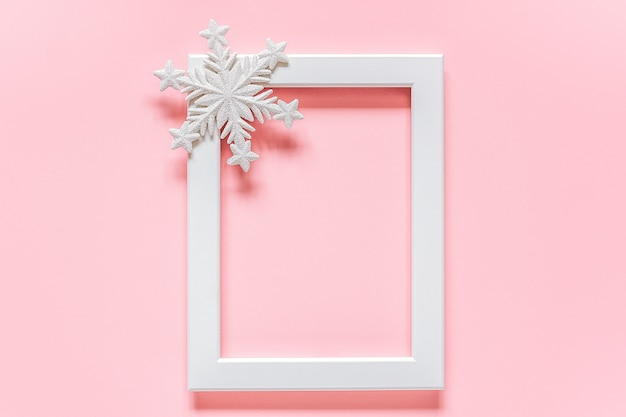 Weißer rahmen mit dekorationsschneeflocke auf rosa hintergrund mit kopienraum