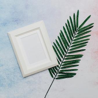 Weißer rahmen mit palmeblatt