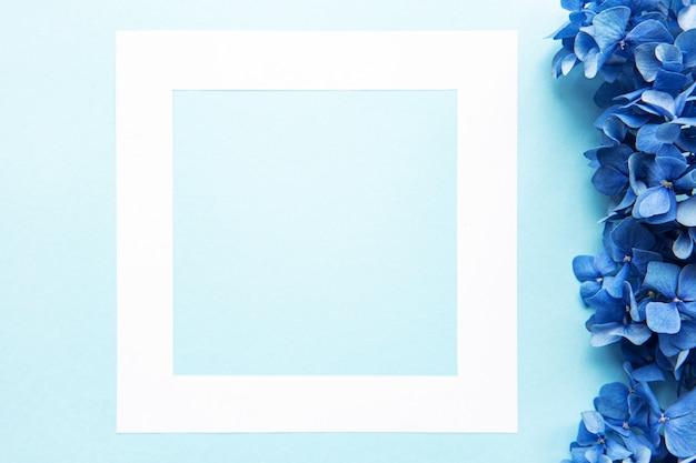Weißer rahmen und blaue hortensie blüht auf blauem hintergrund