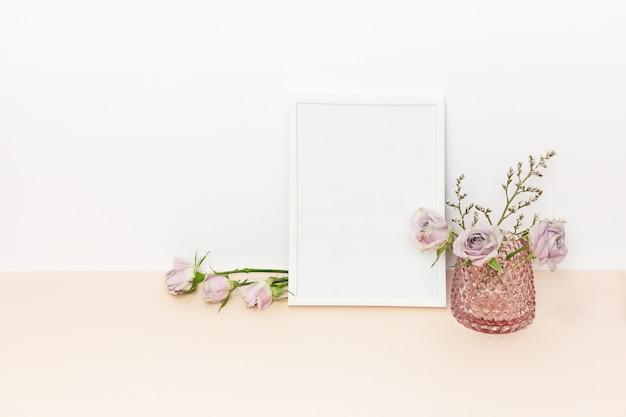 Weißer rahmen und rosa rosen auf dem schreibtisch und der weißen wand