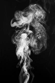 Weißer rauch, der weit über dunklem hintergrund wirbelt