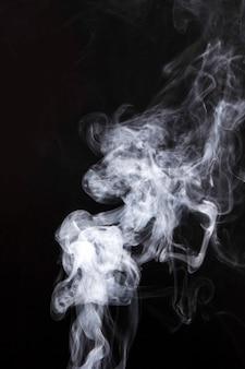 Weißer rauch verbreitet auf schwarzem hintergrund