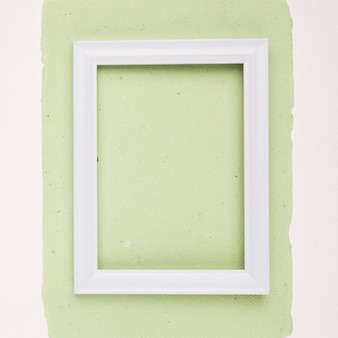 Weißer rechteckiger grenzrahmen auf tadellosem grünbuch auf weißem hintergrund