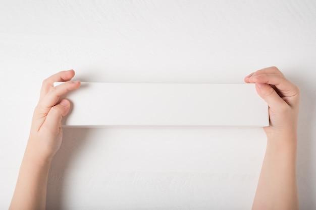 Weißer rechteckiger karton in kinderhänden. draufsicht, weißer hintergrund