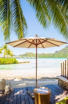 Weißer regenschirm auf hölzernem decking mit sommeransicht des sonnigen strandes von bora bora-insel