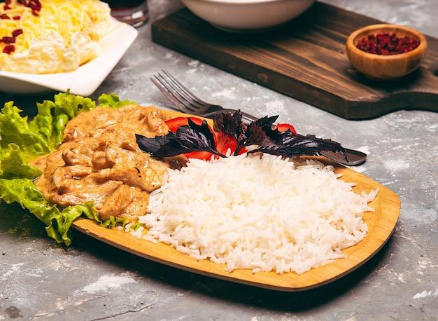 Weißer reis und gemüse der gebratenen hühnertrommelstöcke