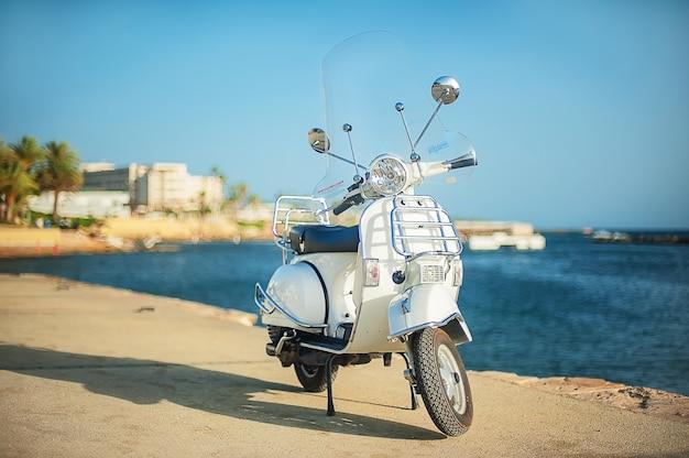 Weißer retro roller am strand. touristische böschung