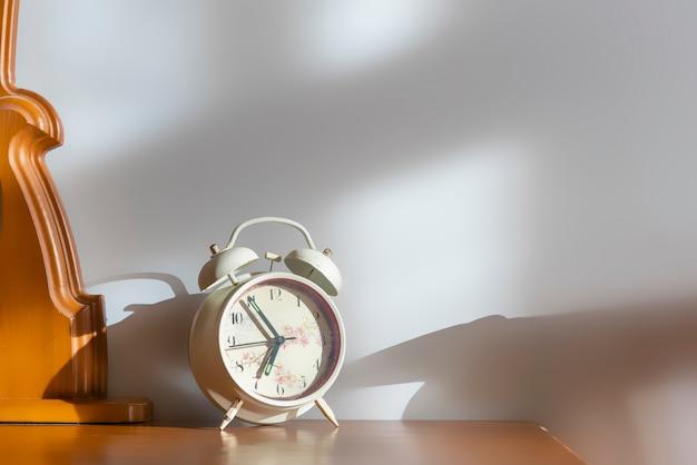 Weißer retro-wecker auf nachttisch am morgen f