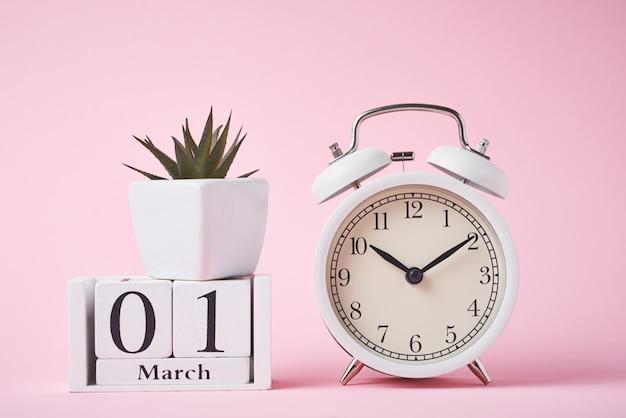 Weißer retro-wecker auf roten und hölzernen kalenderblöcken mit datum 1. märz auf dem rosa. zeitkonzept