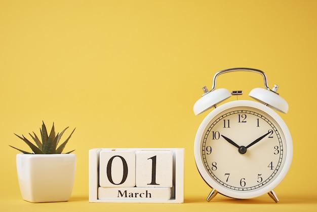Weißer retro-wecker auf roten und hölzernen kalenderblöcken mit datum 1. märz auf gelb. zeitkonzept