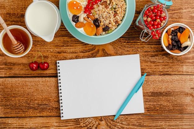 Weißer rohling des ernährungstagebuchs, gesundes frühstück von müsli mit früchten, milch und honig auf holztisch.