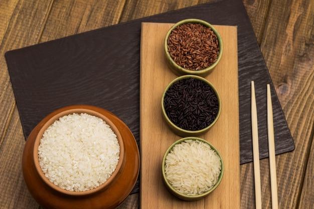 Weißer runder reis im keramiktopf. roter und schwarzer reis in schalen. bambusstöcke auf dem tisch. flach liegen