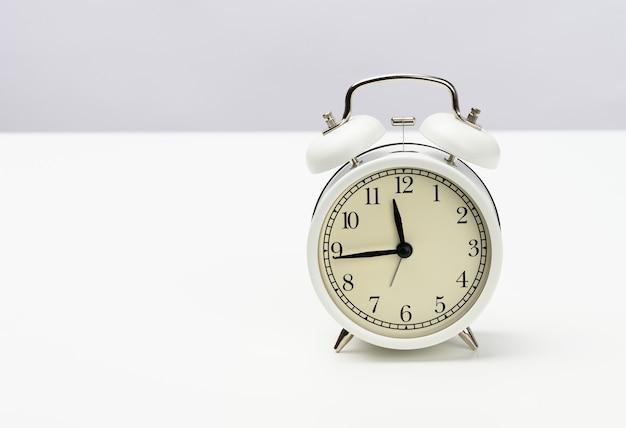 Weißer runder wecker steht auf dem tisch, die zeit ist fünfzehn minuten vor zwölf