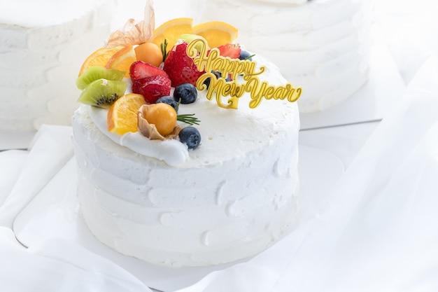 Weißer sahnekuchen mit frohem neuen jahr und gekrönt mit orange, erdbeere, blaubeere und kapstachelbeere auf weißem stoffhintergrund, kopienraum und dessertkonzept
