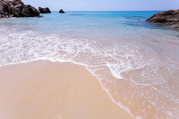 Weißer sand des schönen tropischen seestrandes mit der welle, die auf sandigem ufer zusammenstößt
