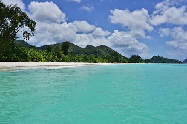 Weißer sandstrand mit türkisfarbenem wasser und blauem himmel mit wolken, indischer ozean, praslin island, seychellen, afrika