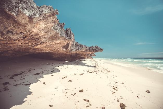 Weißer sandstrand neben dem felsen. indonesien
