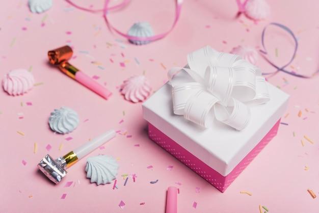 Weißer satinbogen auf geschenkbox mit parteigebläse und süßigkeiten über rosa hintergrund