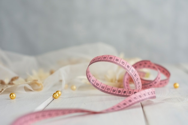 Weißer satinstoff mit zentimeter auf holzhintergrund mit perlen.