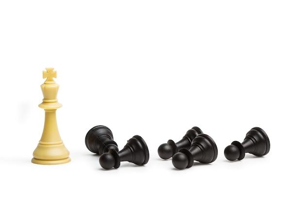 Weißer schachkönig auf einem holzblock und schwarze schachbauern mit kopienraum