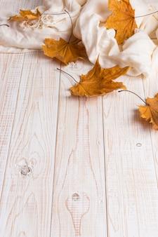 Weißer schal und trockenes gelb verlässt auf einem holztisch. herbst hintergrund, exemplar.
