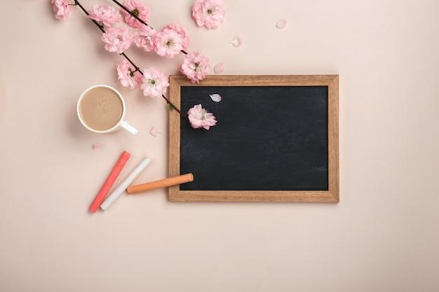 Weißer schalencappuccino mit kirschblüte blüht, kreidebrett auf einem pastellrosahintergrund