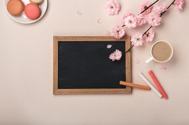Weißer schalencappuccino mit kirschblüte blüht, macarons, kreidebrett auf einem pastellrosahintergrund