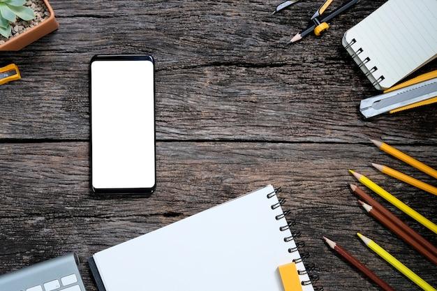 Weißer schirm smartphone auf holztisch- und büroartikel mit tastatur