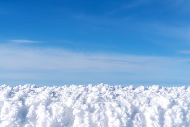 Weißer schnee mit blau klärte himmelhintergrund für anzeigenprodukt oder -montage