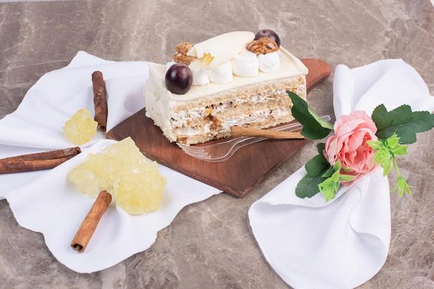 Weißer schokoladenkuchen auf holzbrett mit stoff und süßigkeiten.
