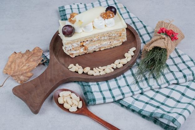 Weißer schokoladenkuchen auf holzbrett mit weihnachtsdekorationen. hochwertiges foto