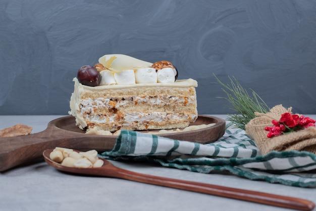 Weißer schokoladenkuchen und löffel erdnüsse auf tischdecke.