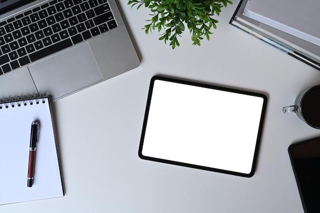 Weißer schreibtisch der draufsicht mit digitaler tablette, laptop und notizbuch.