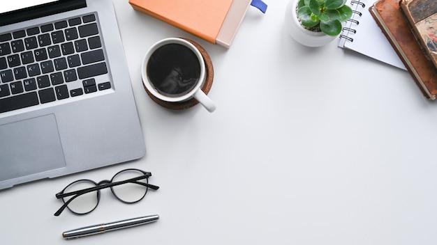Weißer schreibtisch der draufsicht mit laptop-computer, kaffeetasse und gläsern.