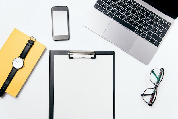 Weißer schreibtisch der draufsicht mit laptop, telefon, notizbuch, klarem papier mit freiem kopierraum und zubehör, flacher hintergrund.